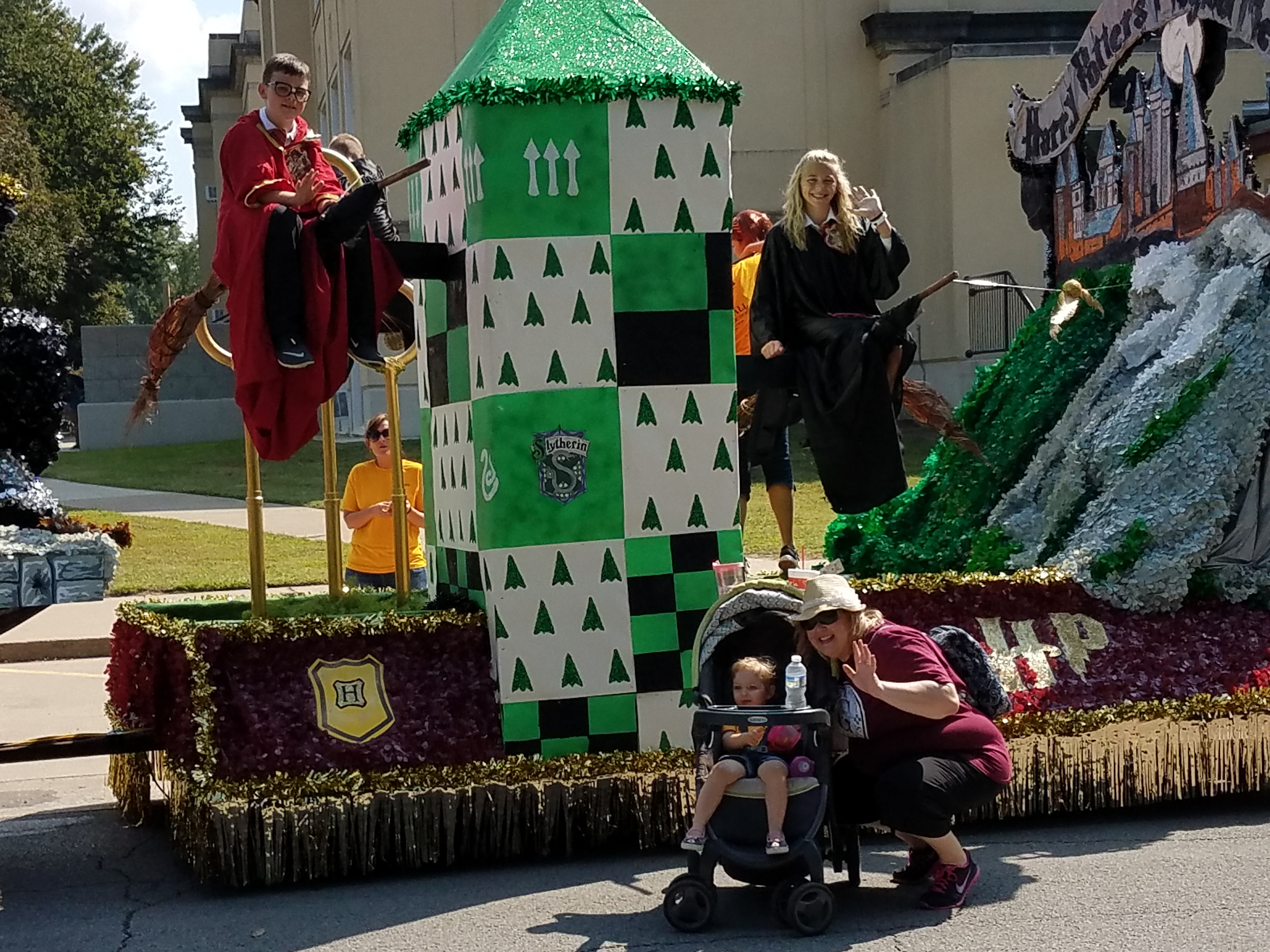 """Murphy-Wall State Bank and Trust Company employees' children dressed as Hogwarts students sit on """"flying"""" broom sticks"""