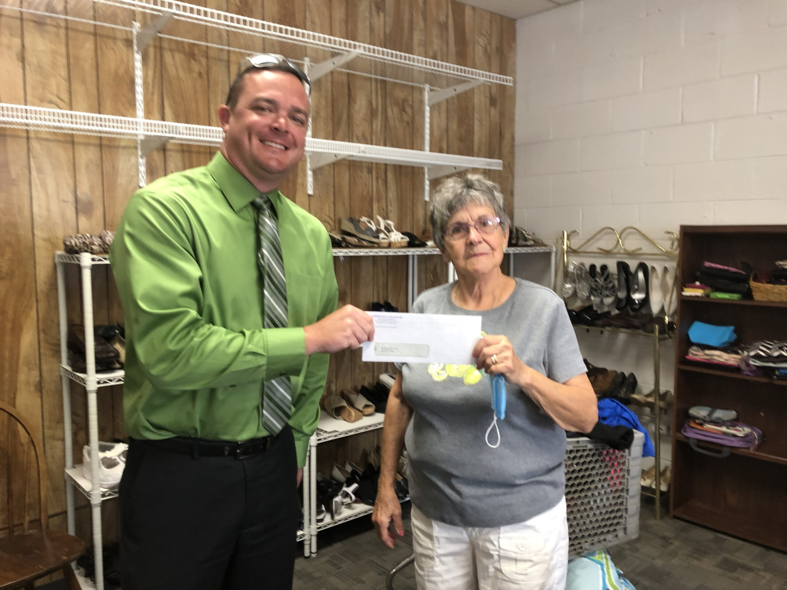 Murphy-Wall VP Kyle Davis gives Community United Pantry volunteer, Sue Phipps