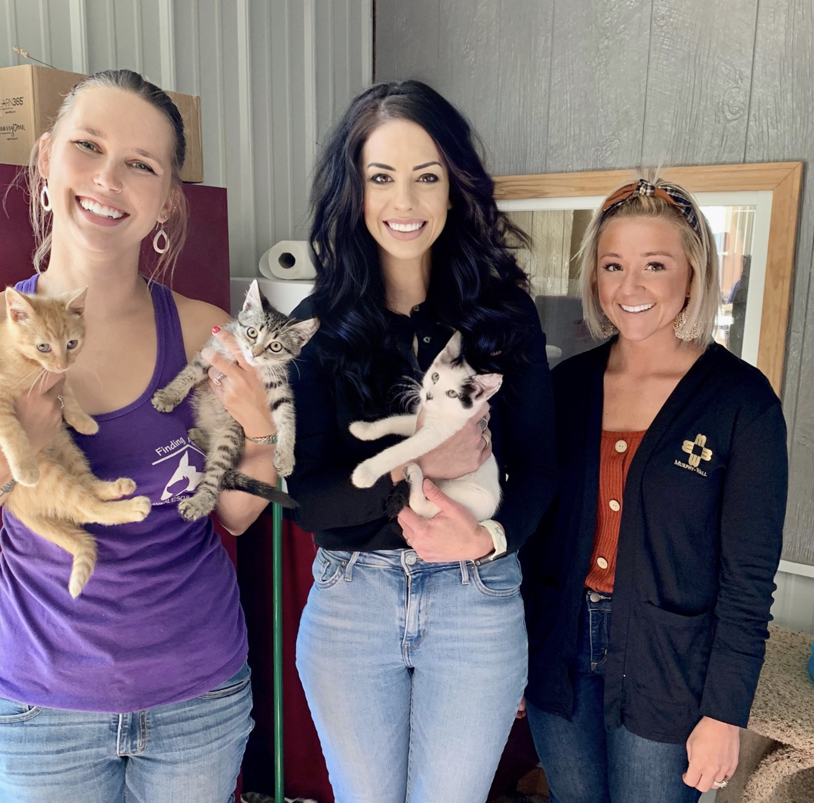 Murphy-Wall State Bank Marion Branch Manager, Bailey Thompson, and Assistant Branch Manager, Ashley Fosse, hold cats while presenting the FHLB COVID relief donation to Finding Forever Animal Shelter of Marion Director, Becca Baird