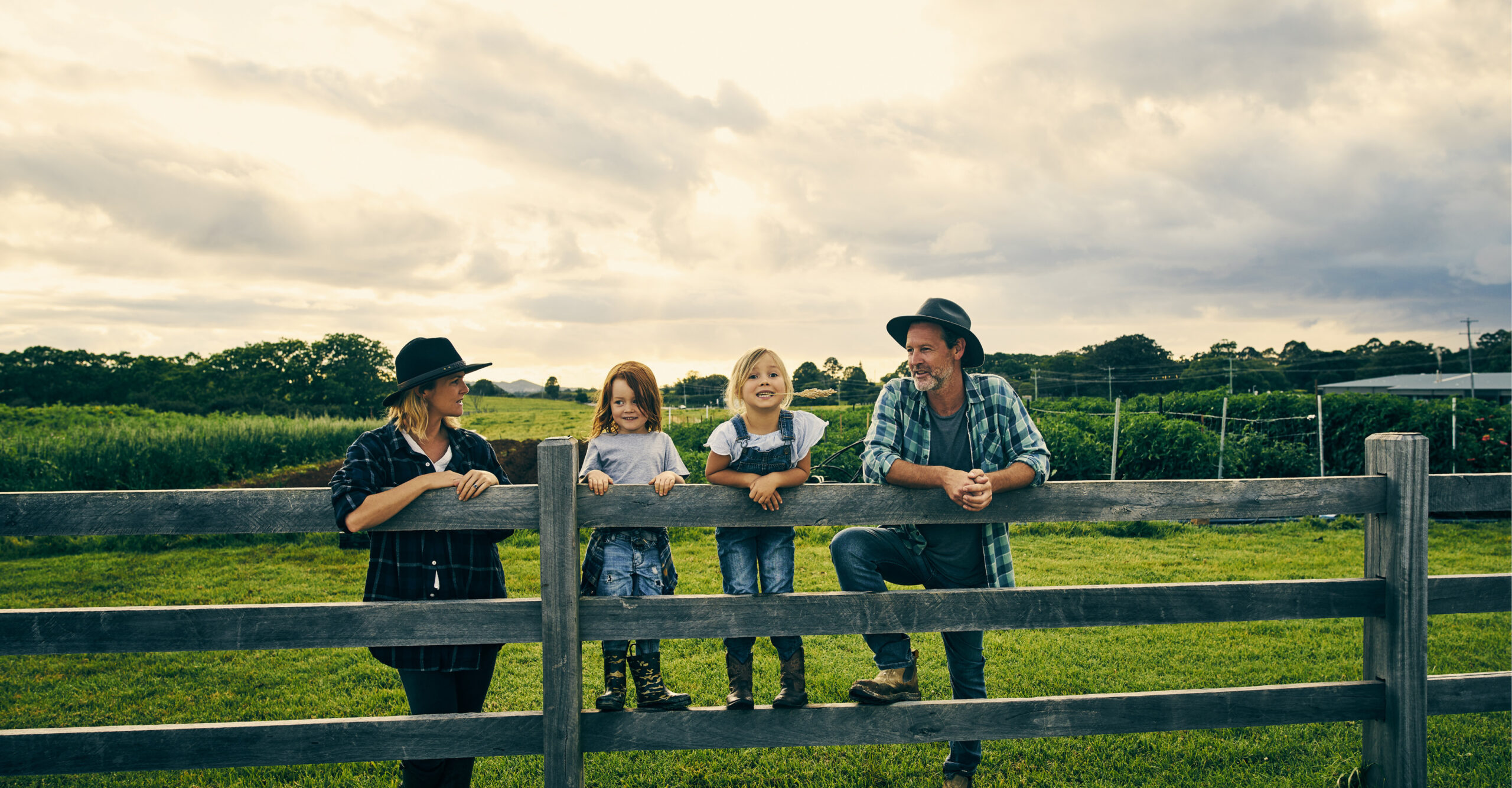 Family on fence post on farm