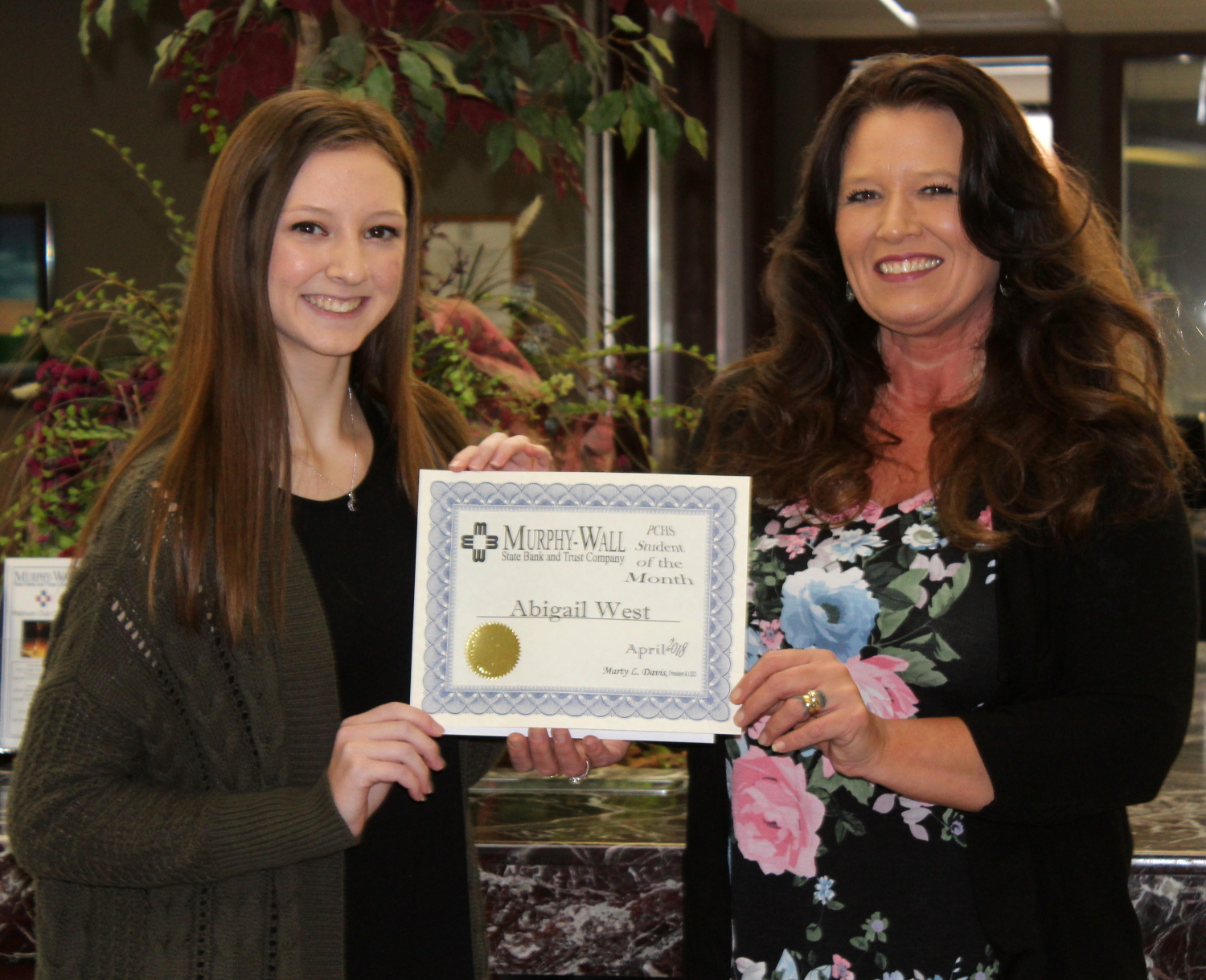 Murphy-Wall State Bank and Trust Company employee Candice Knight give PCHS student Abigail West the 2018 April Student of the Month award