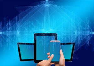 Hands holding smart phone with tablets in the background