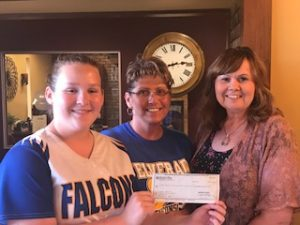 Murphy-Wall State Bank and Trust Company VP Julie Briley gives a donation to Kathy and Ellie Yates for the Elverado softball field
