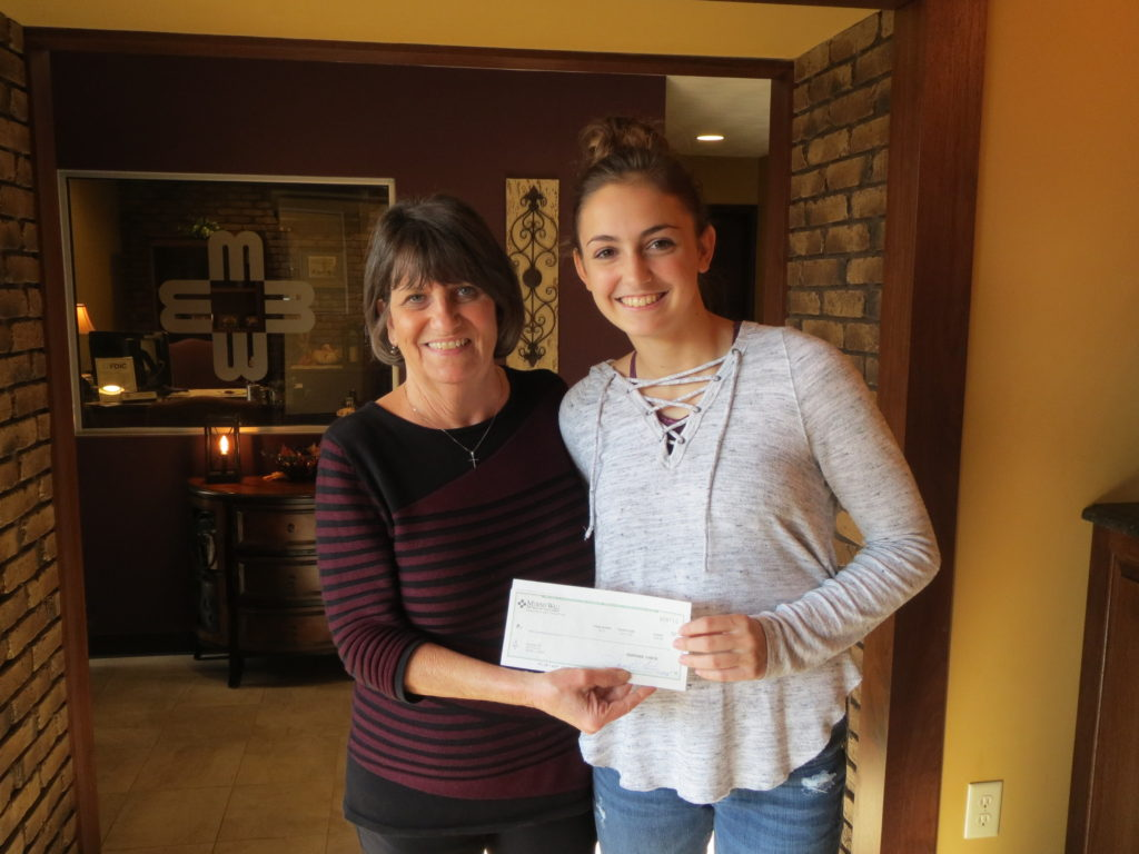 Renee Cobin of Murphy-Wall State Bank's Elkville branch presents Elverado High School FFA Secretary Reese Funk with a donation for the Elverado FFA, in support of their upcoming Elverado FFA Alumni.