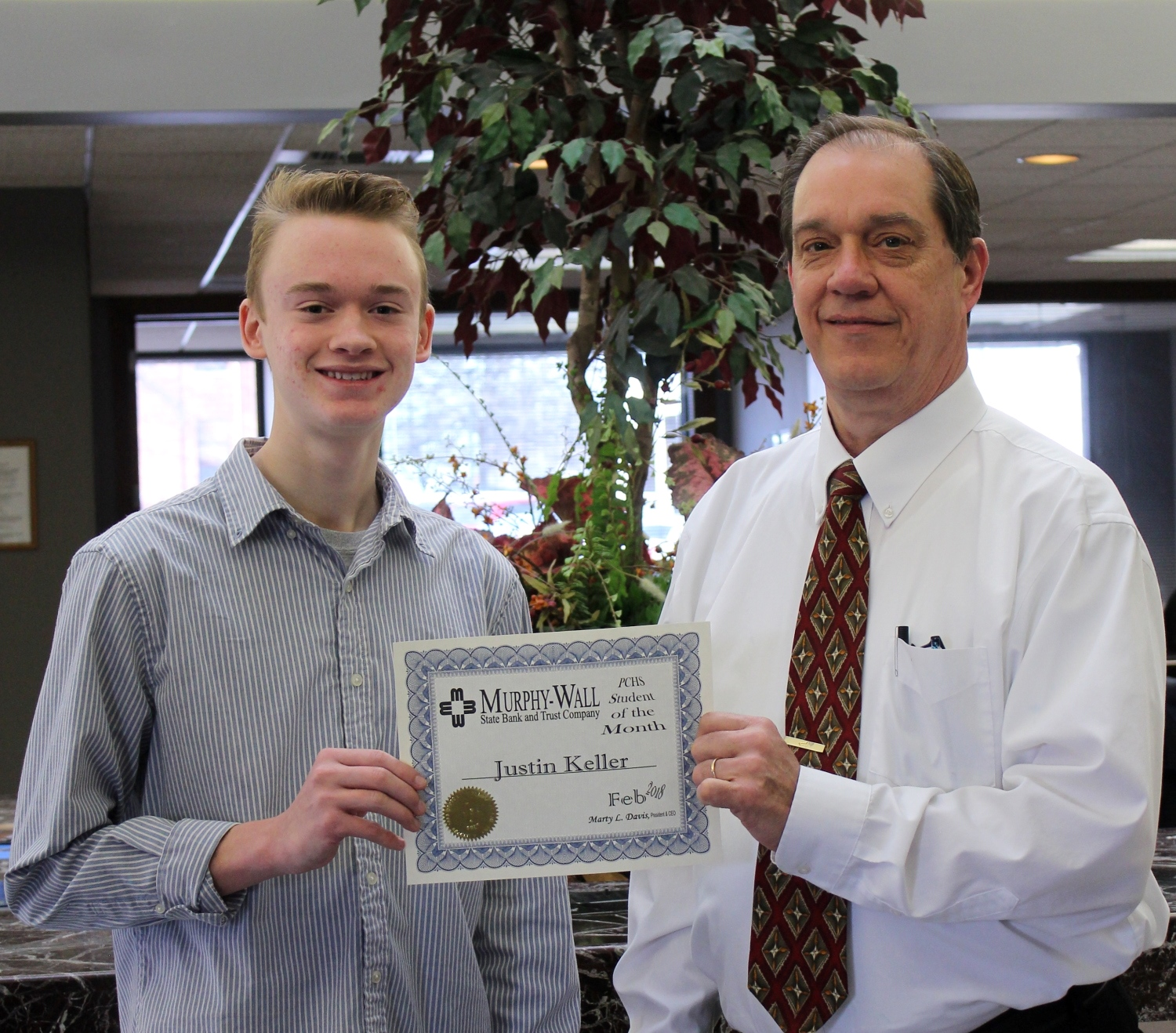 Murphy-Wall State Bank and Trust Company employee Chuck Dobrinick gives PCHS student Justin Keller the 2018 February Student of the Month award