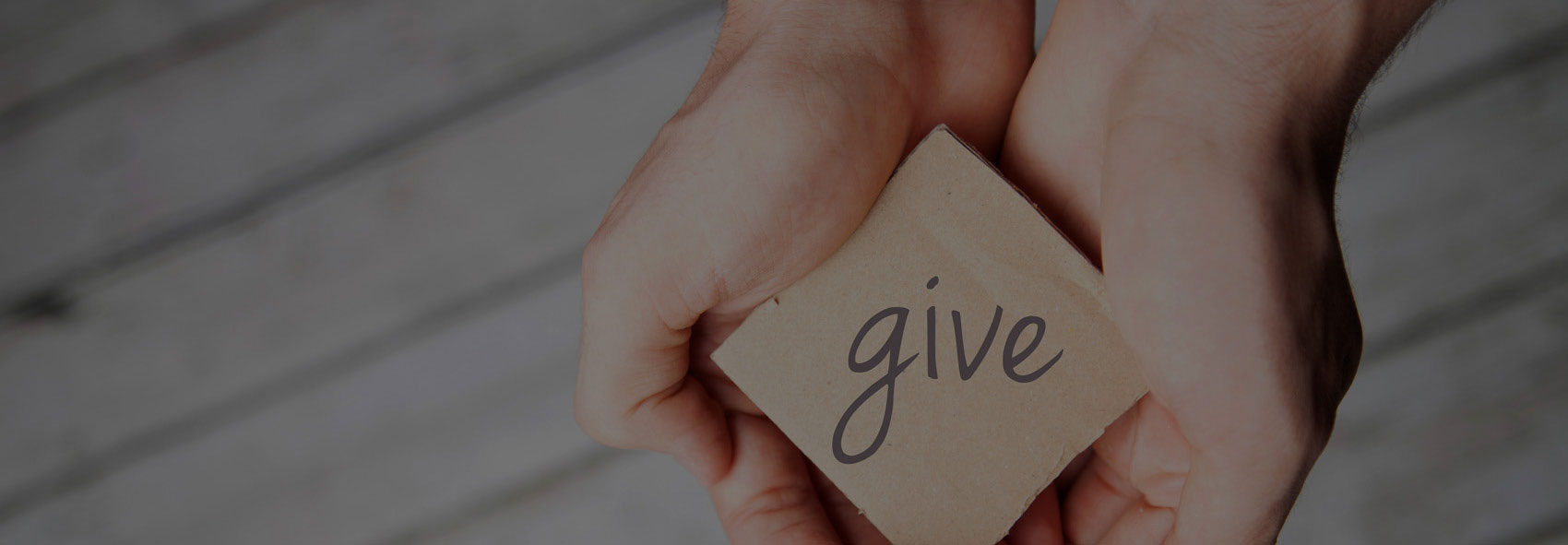 hands holding paper with 'give' on it