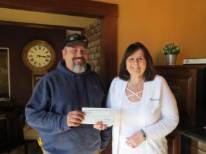 Elverado Fishing Coach Jason Buser accepts a donation from Murphy-Wall State Bank Elkville Branch Manager Julie Briley.
