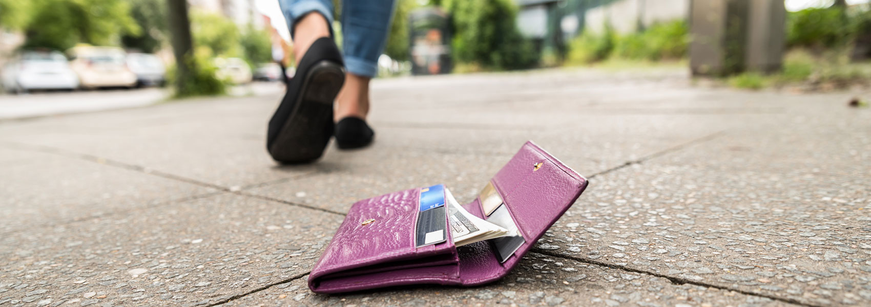 woman walking away from dropped wallet