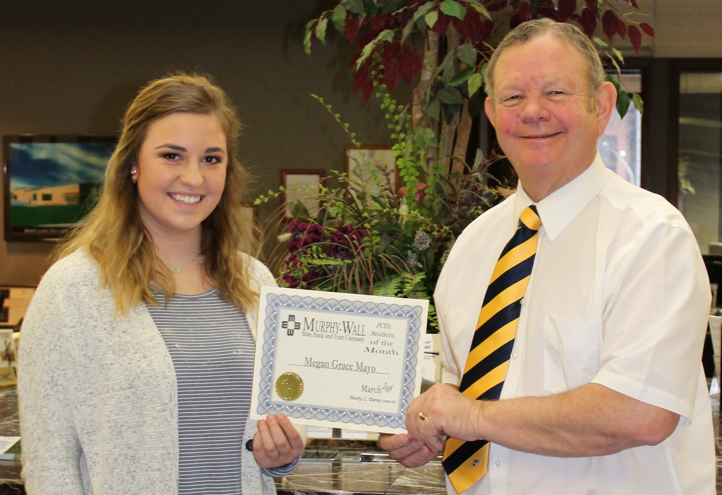 Murphy-Wall State Bank and Trust Company employee Roger Hileman gives PCHS student Megan Mayo the 2018 March Student of the Month award