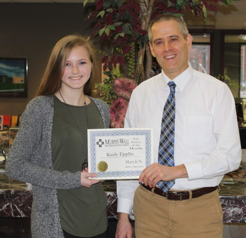 Murphy-Wall State Bank employee Brian Chandler gives PCHS studen Keely Epplin the 2019 March Student of the Month Award