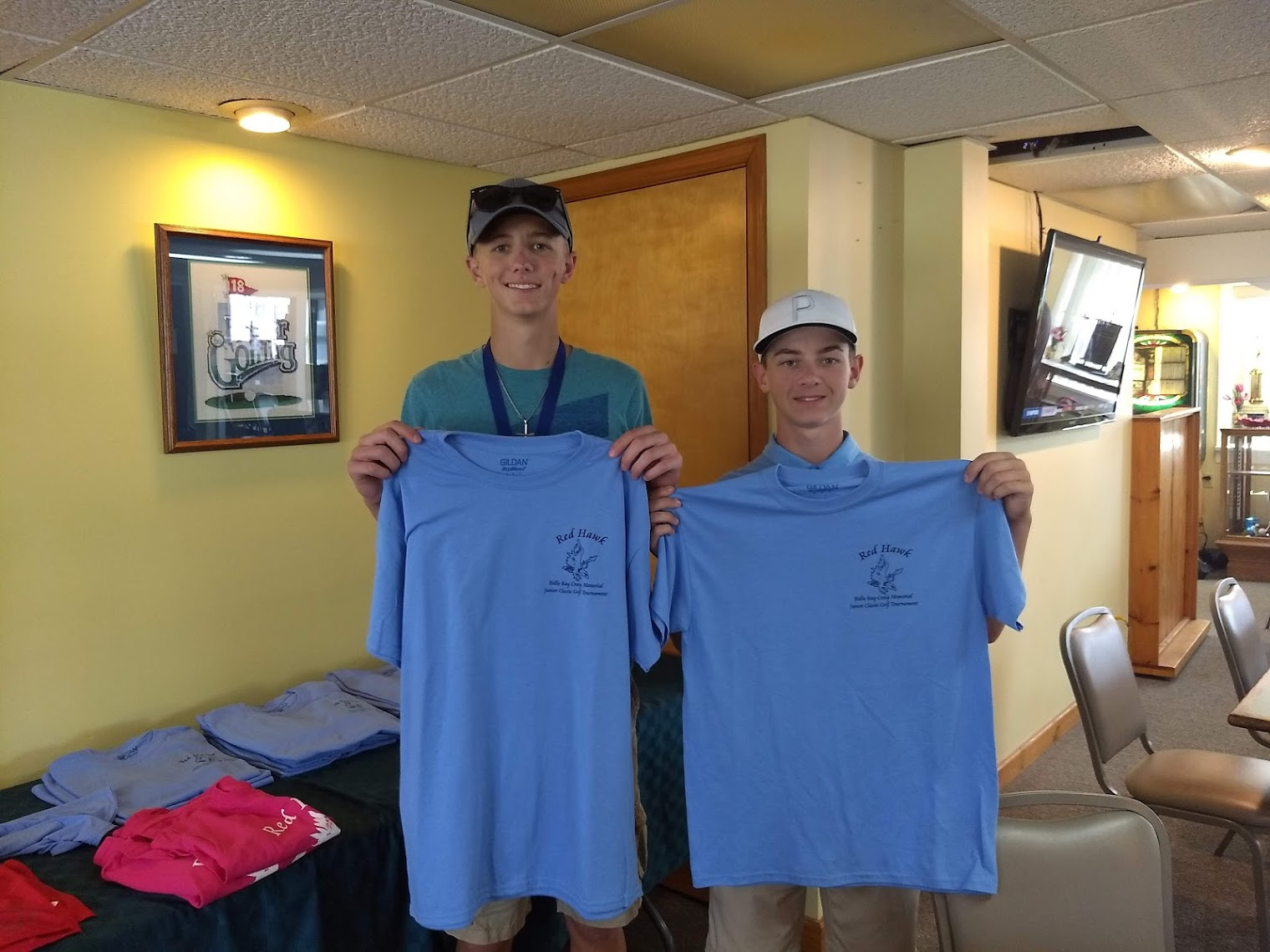 Nile Adcock and Jimmie Reiman hold the Murphy-Wall sponsored shirts at the Billie Ray Craig Memorial Jr Golf Classic