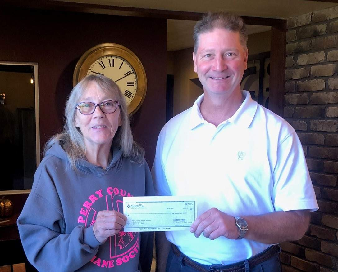 Murphy-Wall State Bank employee Gary Mowry give Perry County Humane Society worker Cheryl Grassel a donation