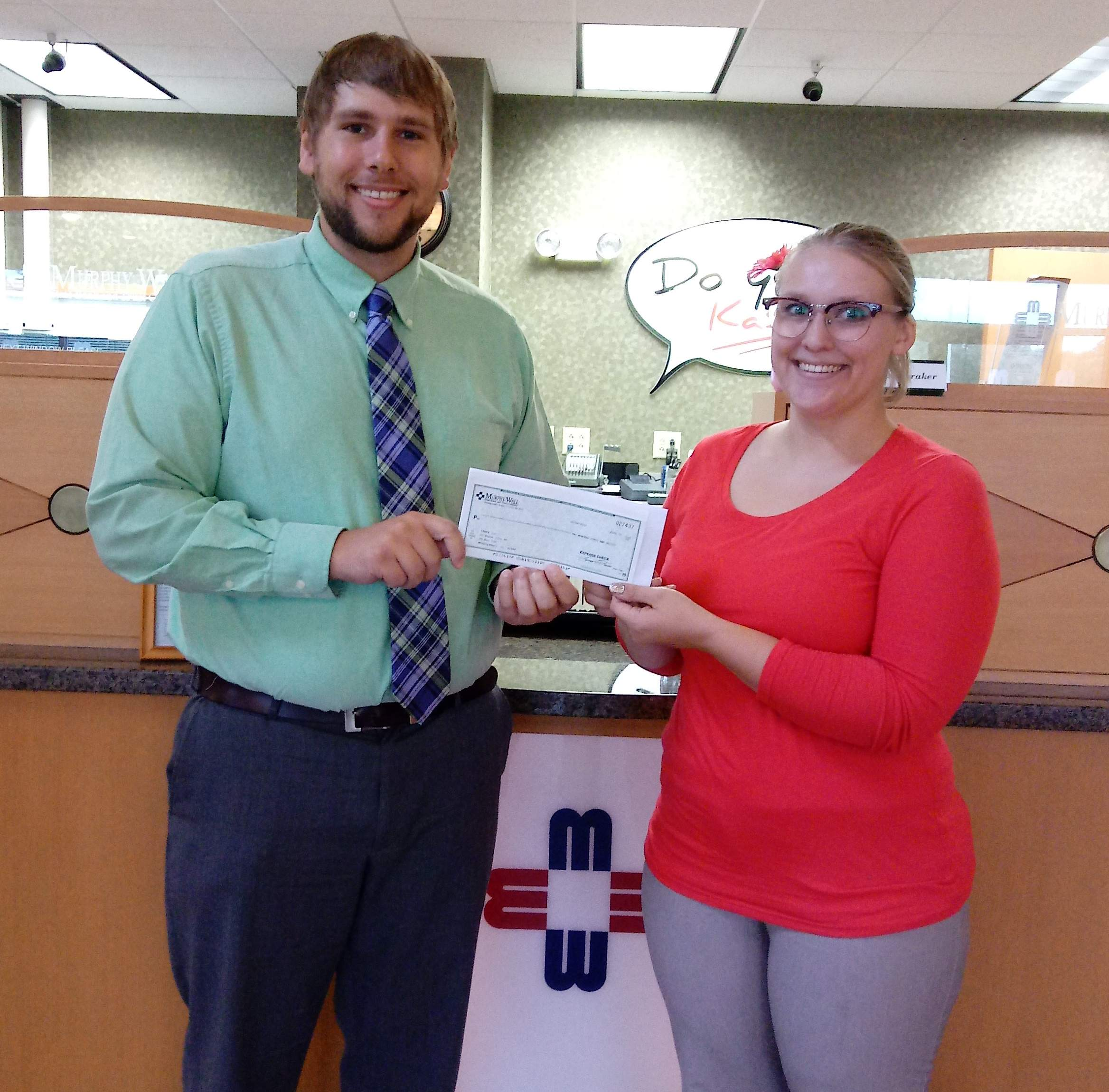 Murphy-Wall State Bank AVP Josh Rakers give donation to START representative Kaitlyn Mifflin