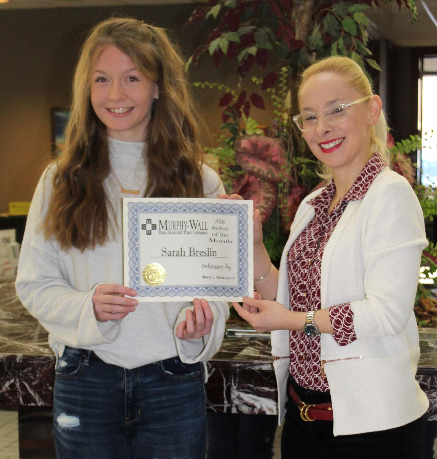 Murphy-Wall State Bank employee Monika Holder give PCHS student Sarah Breslin the 2019 January Student of the Month Award