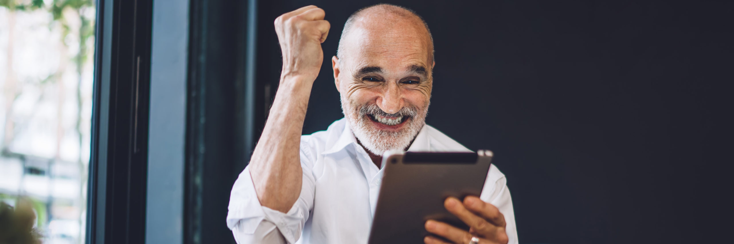 Man with tablet excited and happy with fist in the air