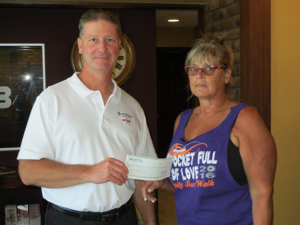Murphy-Wall State Bank and Trust Company AVP Gary Mowry give donation to Shrine Club representative Cheryl Gassel