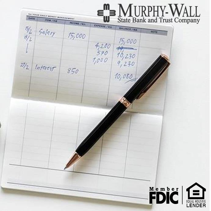 check book register with pen and transactions