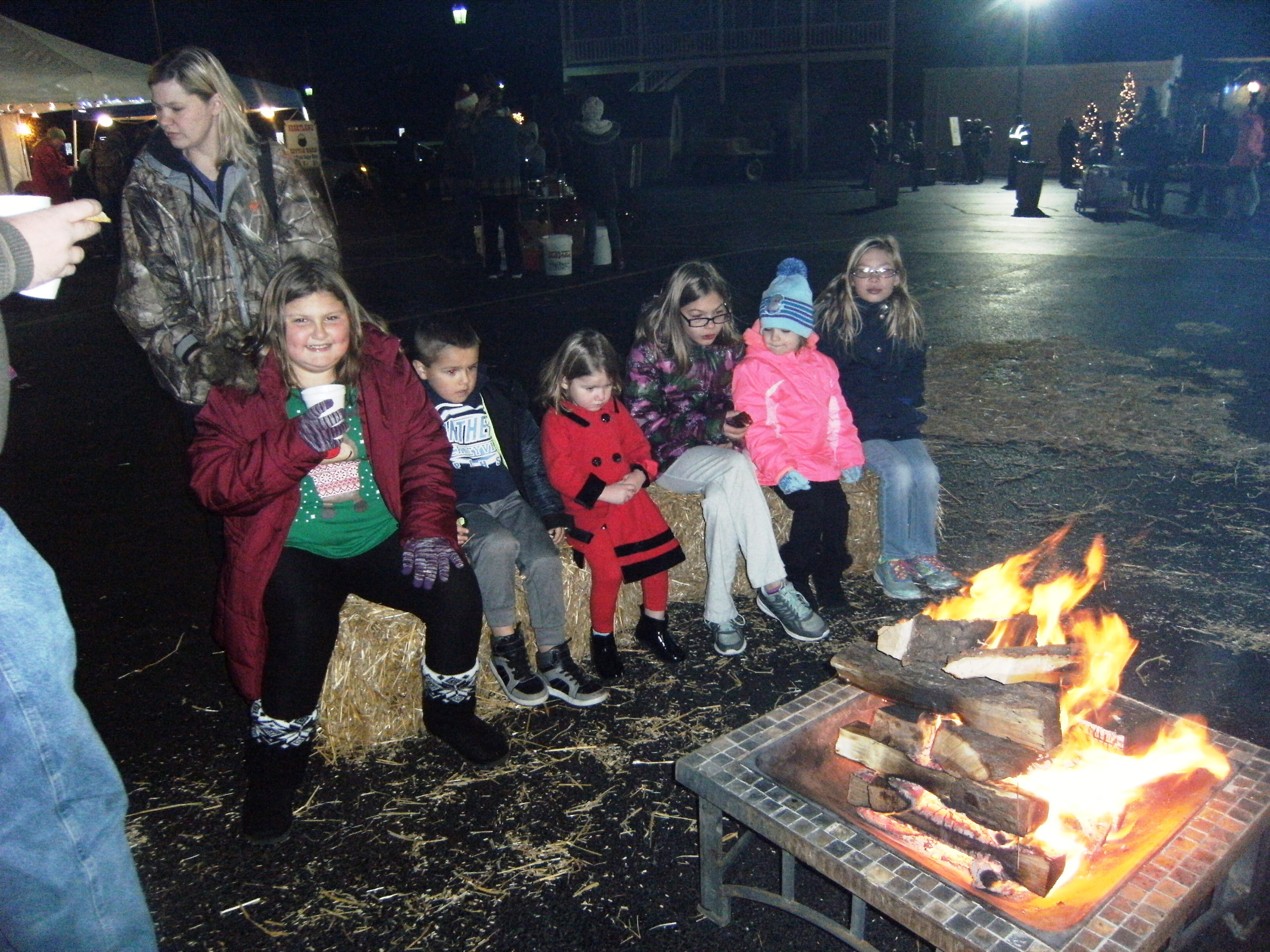 Guests at Murphy-Wall State Bank and Trust Company's Christmas Event hudle around the fire