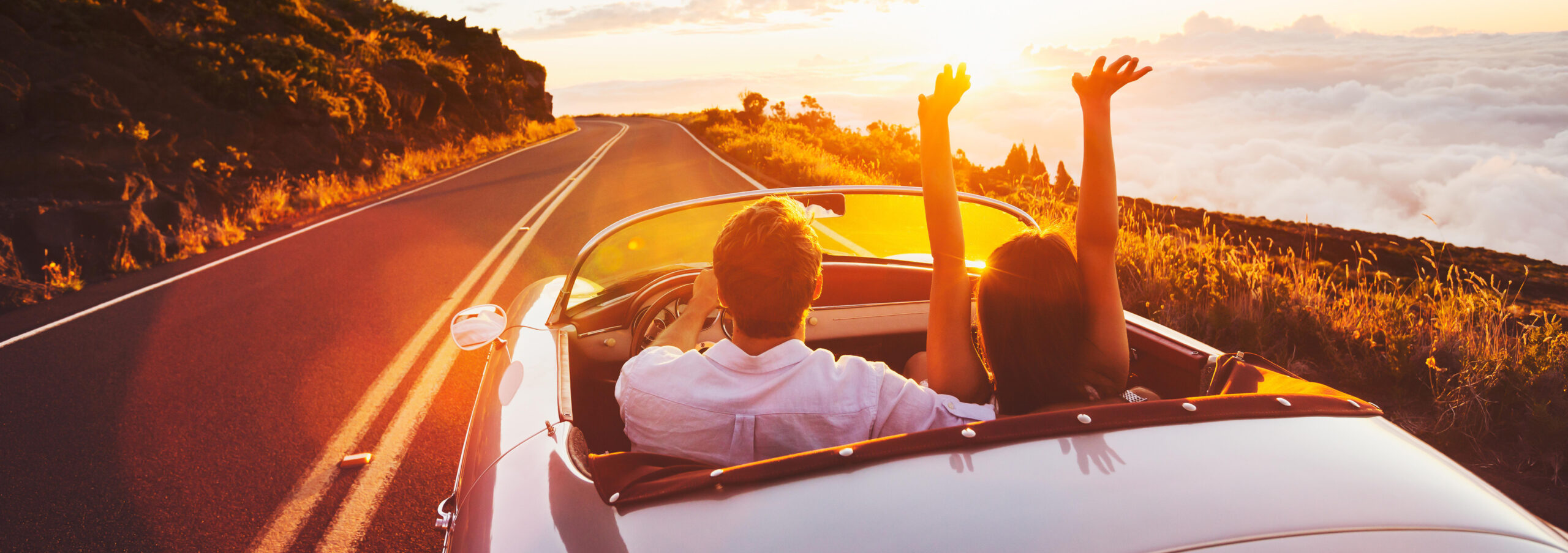Man and women in convertible on open road