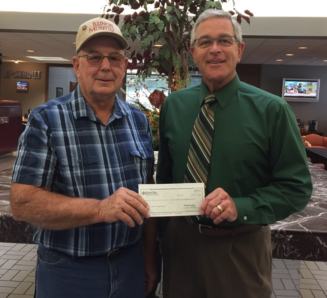 Murphy-Wall State Bank President Marty Davis hands Charlie Greer of the Illinois Rural Heritage Museum a contribution check