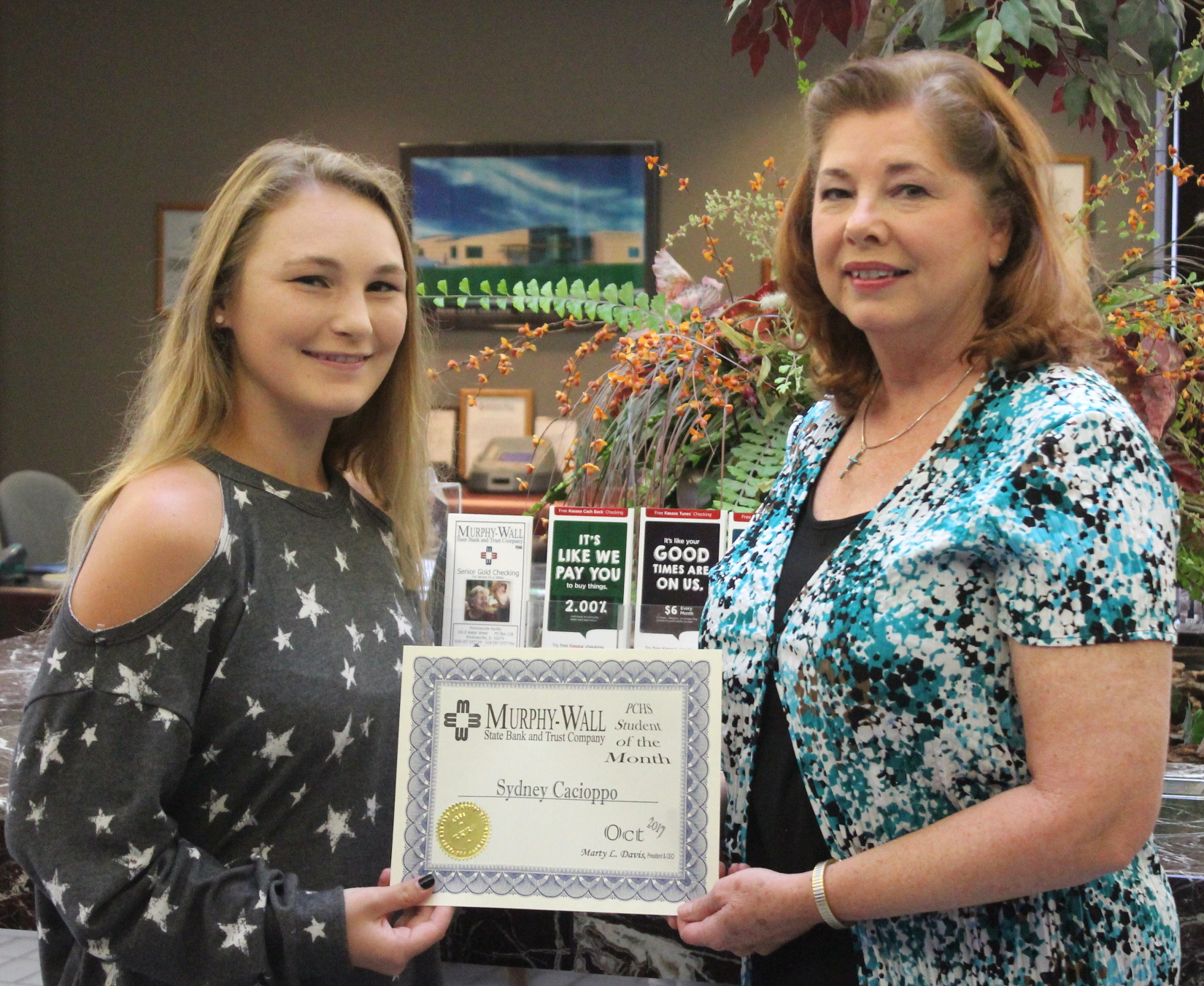 Murphy-Wall employee Kathy Marlow handing the Student of the Month Award to PCHS student Sydney Cacioppo