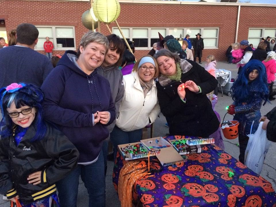 Murphy-Wall State Bank employees smile while passing out finger lights to the trick or treaters