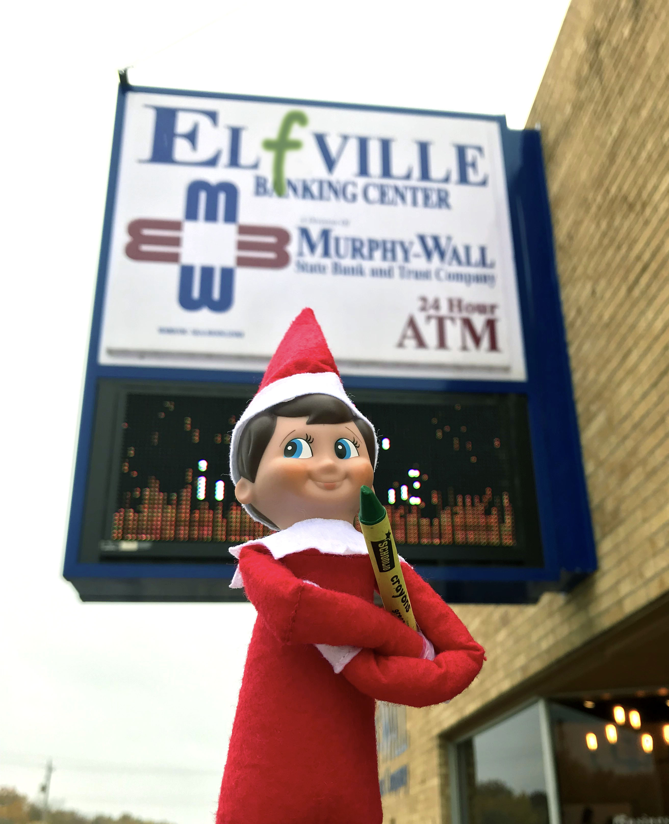 Murph the Elf stands infront of the Elkville banking location after changing the sign to