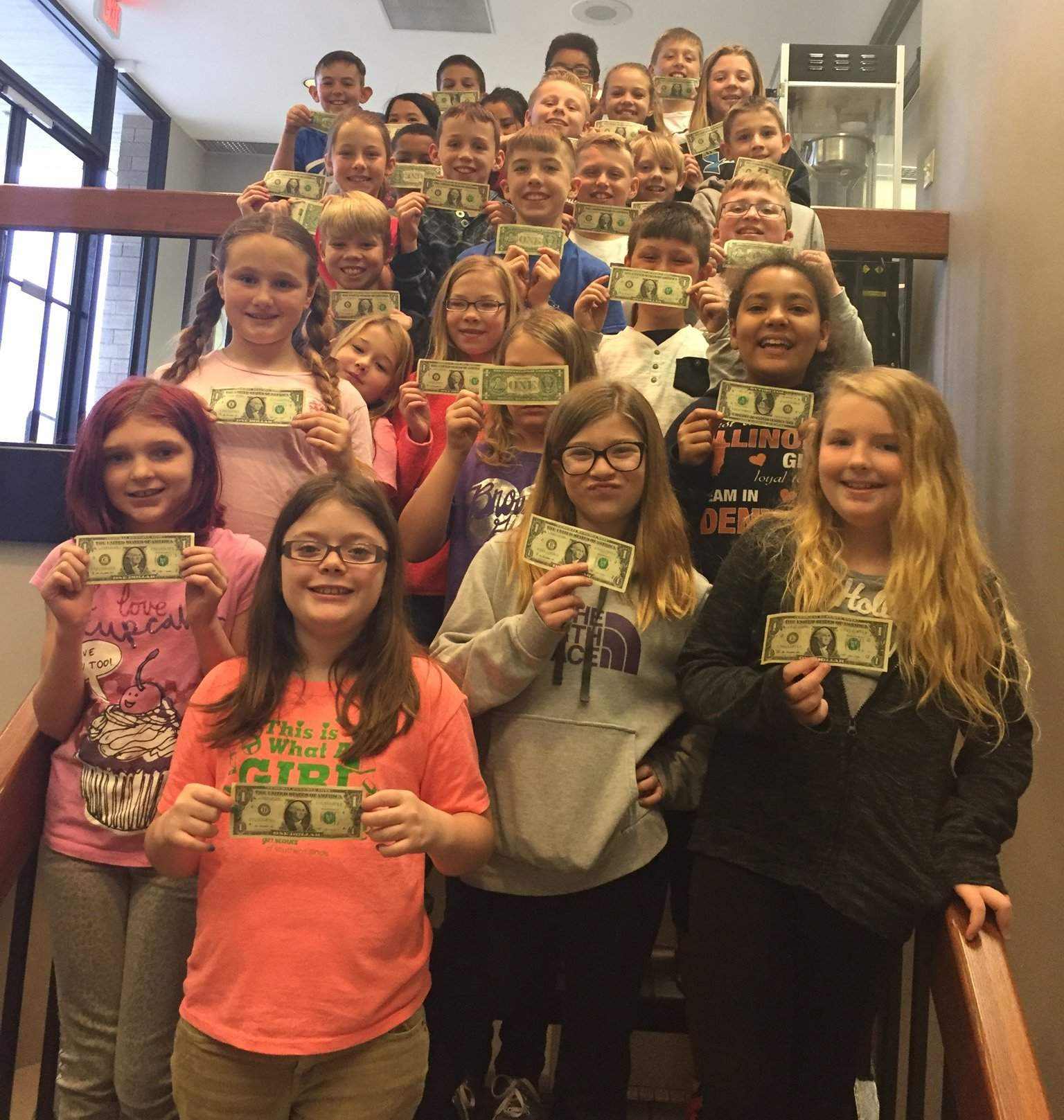 Mrs. Rheinecker's 4th grade students pose with their dollar bills at Murphy-Wall State Bank and Trust Company's 2018 Financial Education