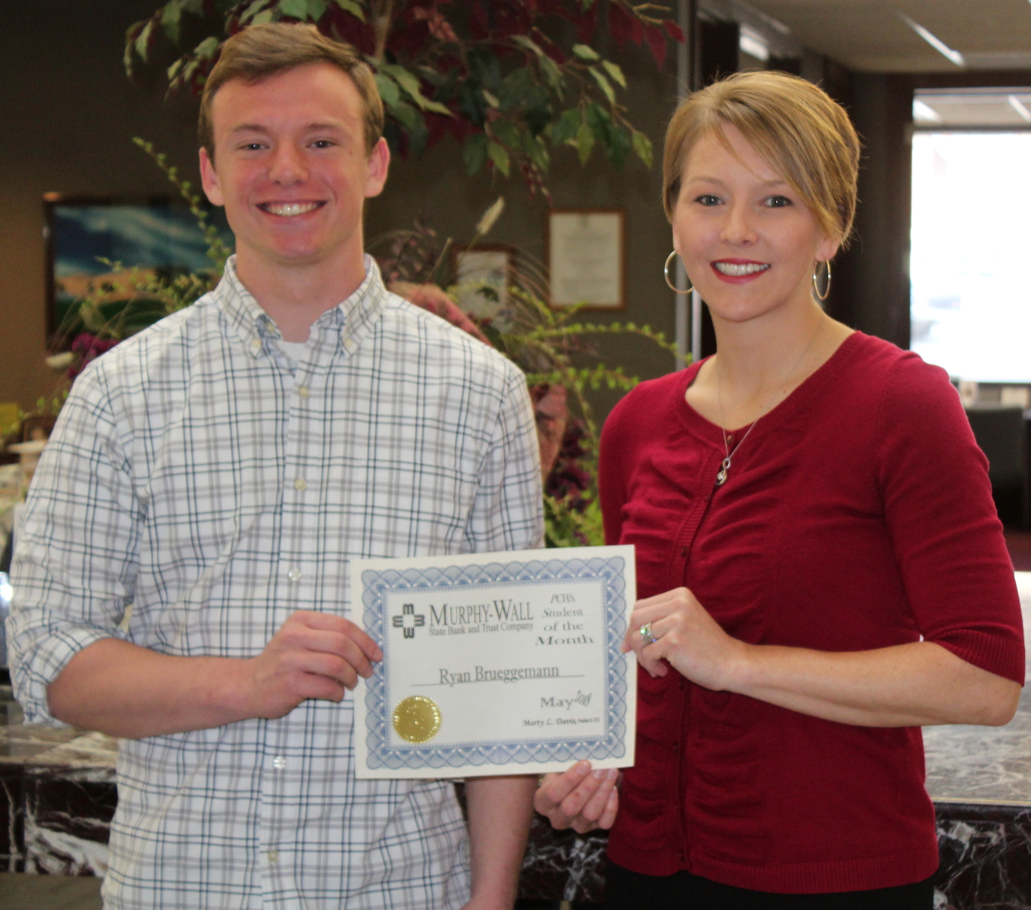Murphy-Wall State Bank and Trust Company employee Sarah Folden gives PCHS student Ryan Brueggemann the Student of the Month award for May 2018
